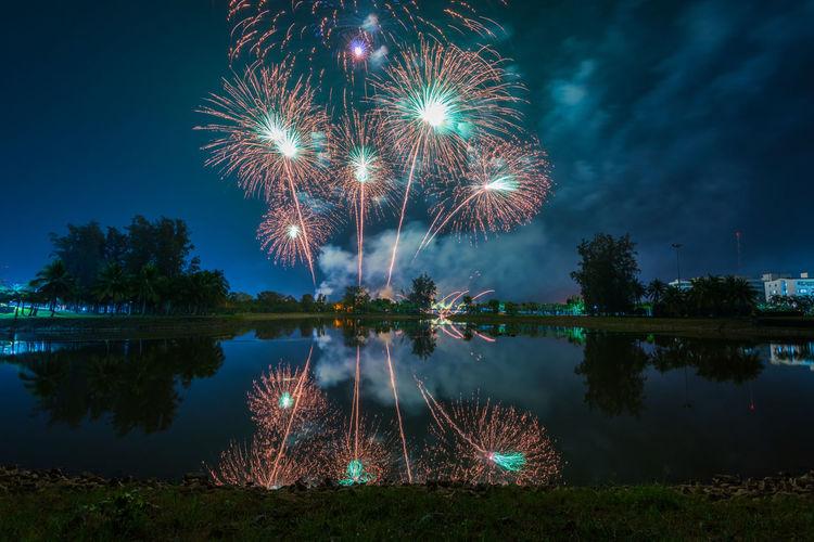 Firework display over lake at night