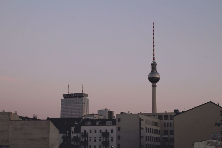 Fernsehturm Amidst Buildings Against Clear Sky In City