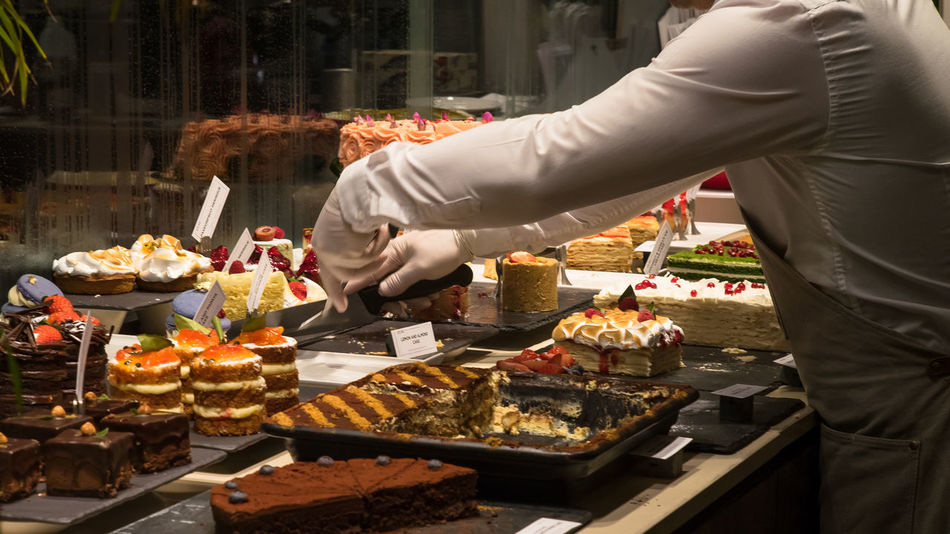 Chef serving cakes among a variety of cakes Cakes Sugar Treat Yourself Cake Confectionery Delicious Display Options Patisserie Selection Sugary Sweet Sweet Food Sweets Treat Variety Yummy Modern Workplace Culture