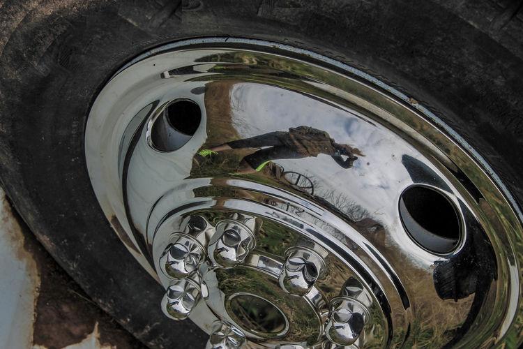 High angle close-up of woman reflecting on wheel rim