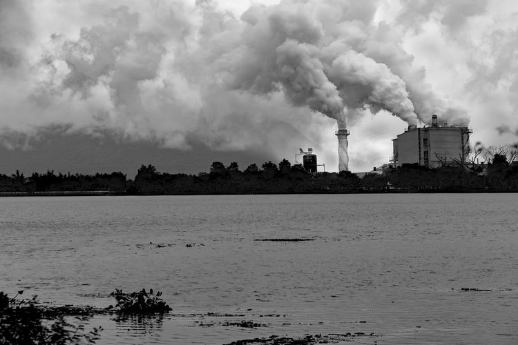 Air Pollution Atmospheric Building Exterior Built Structure Day Ecosystem  Emitting Environment Environmental Damage Environmental Issues Factory Fumes Industry Nature No People Outdoors Pollution Sky Smoke Smoke - Physical Structure Smoke Stack Water