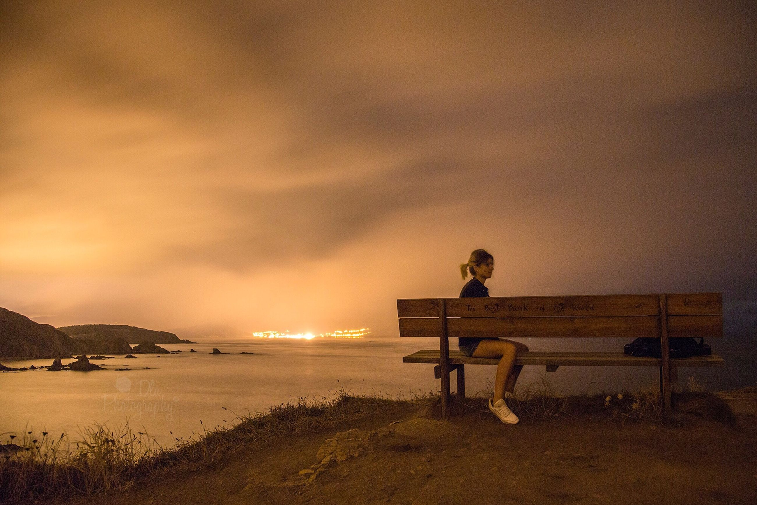 bench, sitting, rear view, men, full length, cloud, relaxation, water, illuminated, night, cloud - sky, sky, tranquil scene, orange color, tranquility, solitude, calm, sea, scenics, remote, escapism, person, outdoors, park bench