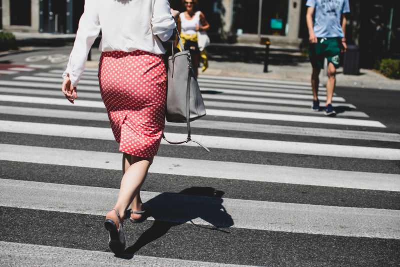 Low section of woman walking zebra crossing during sunny day