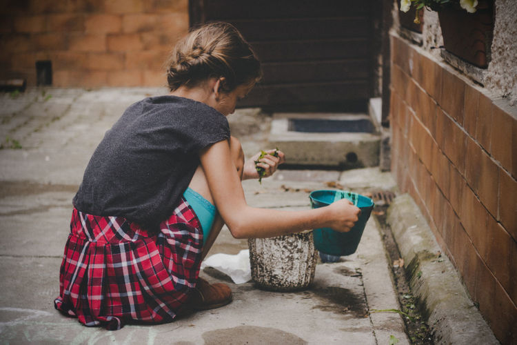 Girl holding bucket while crouching outdoors