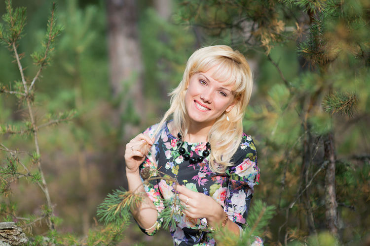 Portrait of young woman holding leaves in forest