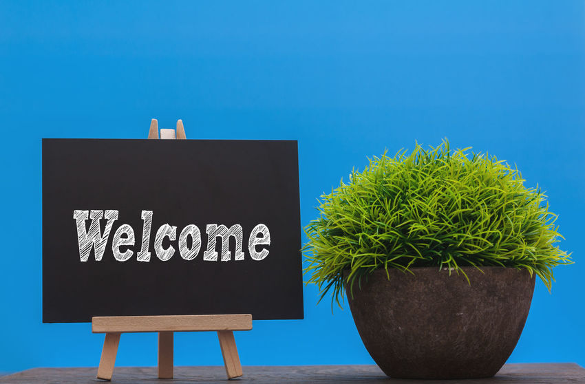 Welcome word on blackboard with green artificial grass with blue background Blackboard  Blue Close-up Communication Day Growth Nature No People Outdoors Plant Road Sign Sky Text Welcome Sign