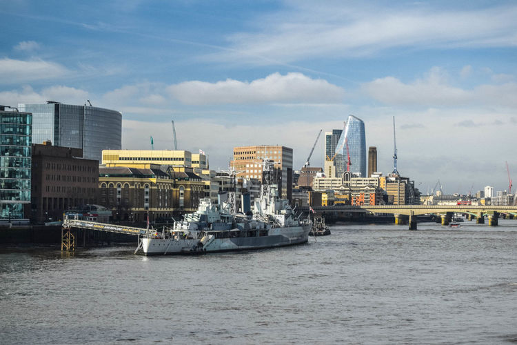 View of hms belfast and london southbank against blue sky with thames in foreground.