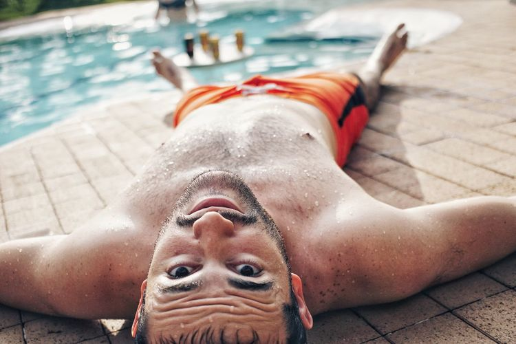 Portrait of shirtless man lying down by swimming pool