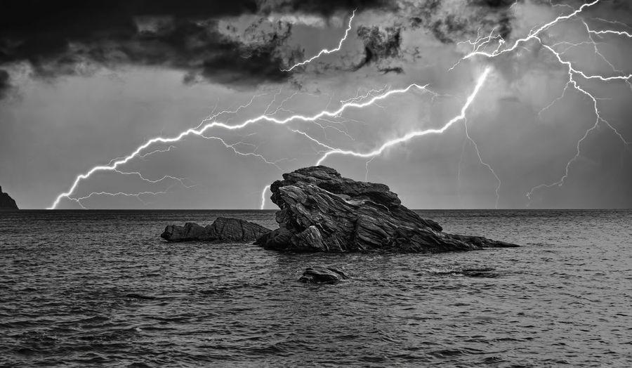 Panoramic shot of rock in sea against sky