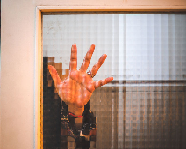 Midsection of person hand on glass