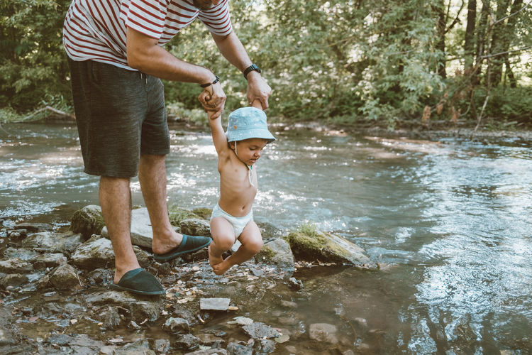 Low section of father holding son by stream in forest