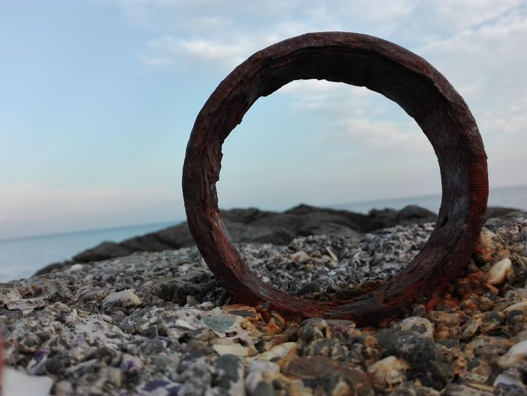 Beach Blue Day Landscape Look Through Look Through The Lens. Metal Ring Metal Rings Nature No People Outdoors Pebbles And Stones Ring Rings♥ Rock - Object Rusted Rusty Rusty Goodness Rusty Metal Rusty Things Sand Sea Sea And Rusty Metal Sky Travel Miles Away