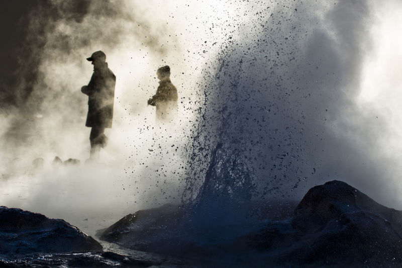 People amidst geyser