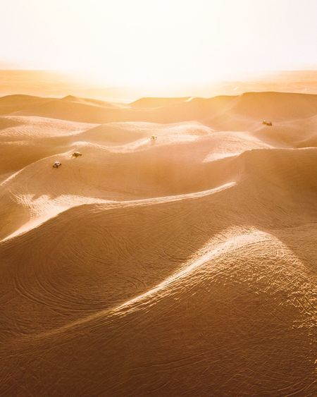Bright sunlight shining over the dunes in glamis california as dune buggies race across the sand