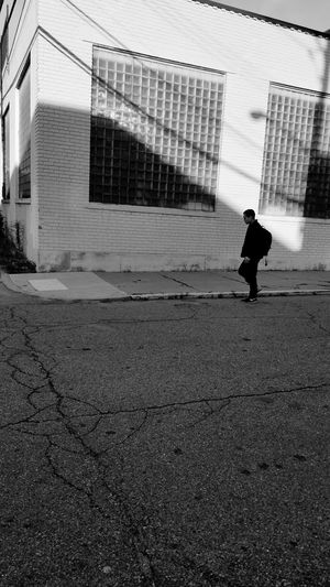 Black & White Real People Light And Shadow Built Structure Building Exterior Adult Outdoors Day One Person Cityscapes BookbagIsPacked Walking On The Street Side View Brick Wall Going To Class