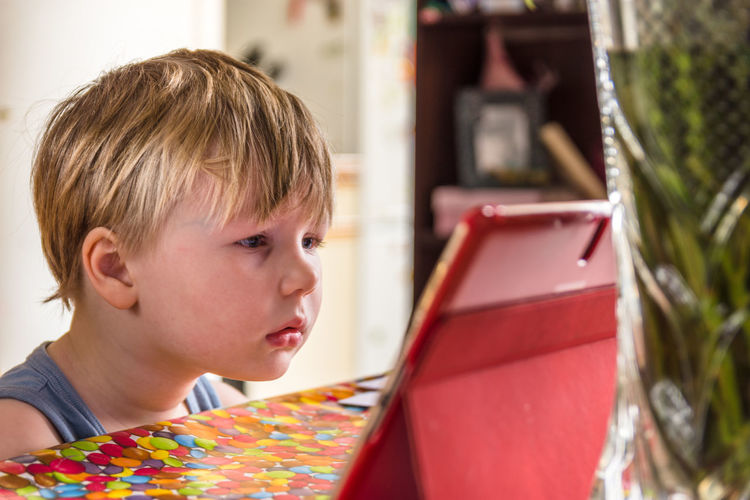 Little Boy watching digital tablet with face expression Blond Hair Boys Childhood Close-up Computer Computer Keyboard Day Dissapointed Expression Façade Focus On Foreground Headshot Indoors  Lifestyles Looking At Camera One Person People Real People Table Unhappy Watching