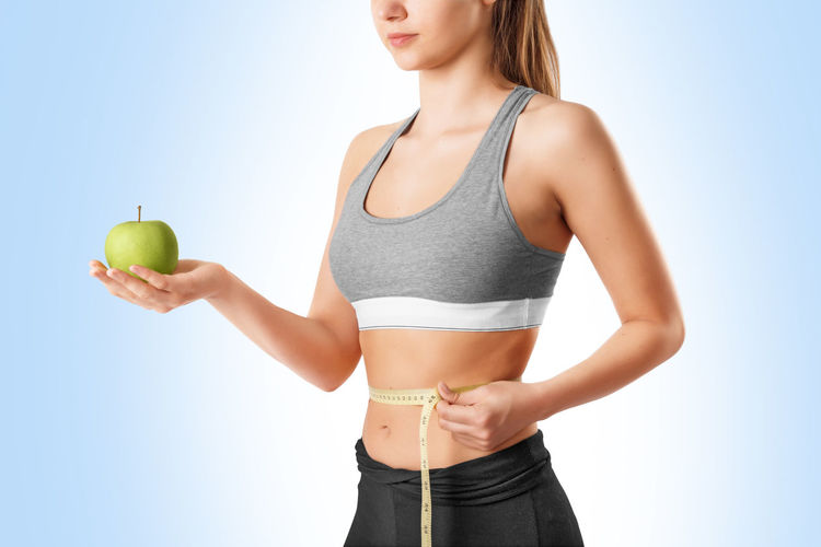 Midsection of young woman holding apple while measuring waist against white background