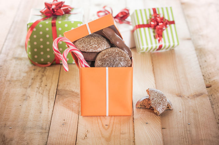 Top open gift box full of gingerbread and colorful candies on a wooden table Birthday Gifts Holiday Gifting X-mas Decoration Xmas Candy Cane Celebration Christmas Christmas Decoration Christmas Present Gift Gift Boxes Ready-to-eat Still Life Sweet Food Tied Bow