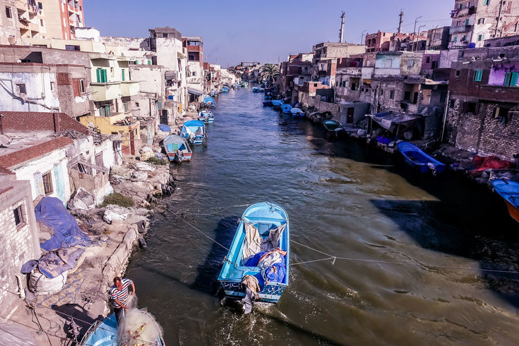 High angle view of boats in canal amidst buildings in city