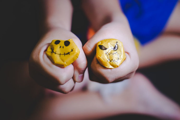 Close-Up Of Child Holding Yellow Scary Faces