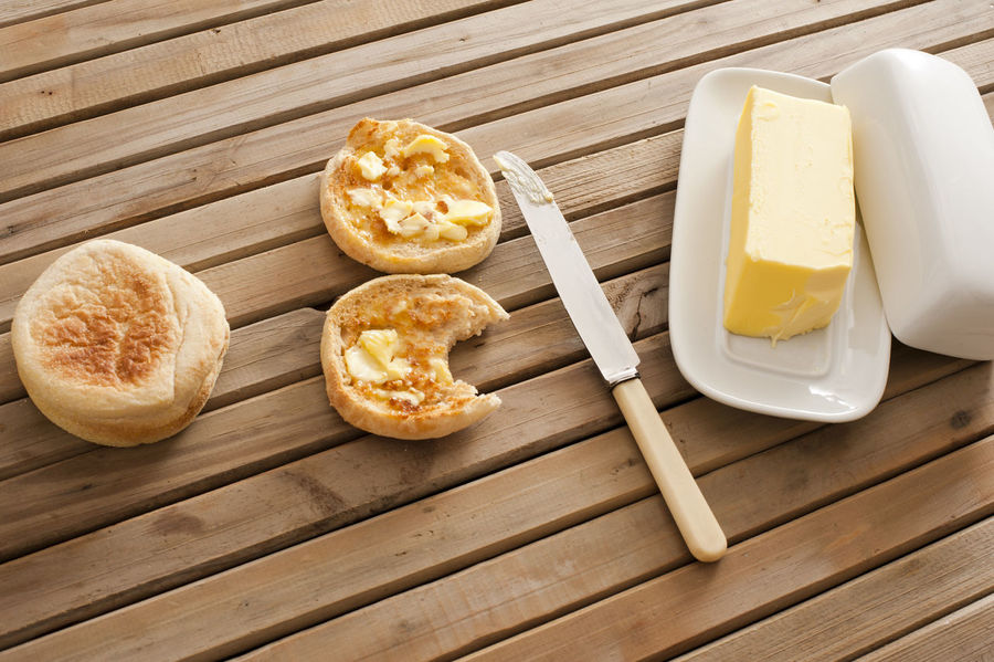 Buttered crumpets, one bitten into, with a pat of farm butter on a wooden slatted table, high angle view Baked Bitten Bread Breakfast Buttered Butterfly Crumpet Dairy Eaten Food Food And Drink Fresh High Angle View Knife Morning Pattern Serving Size Slatted Table Toasted