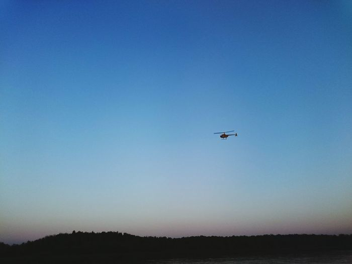Helicopter flying over volga river against clear sky