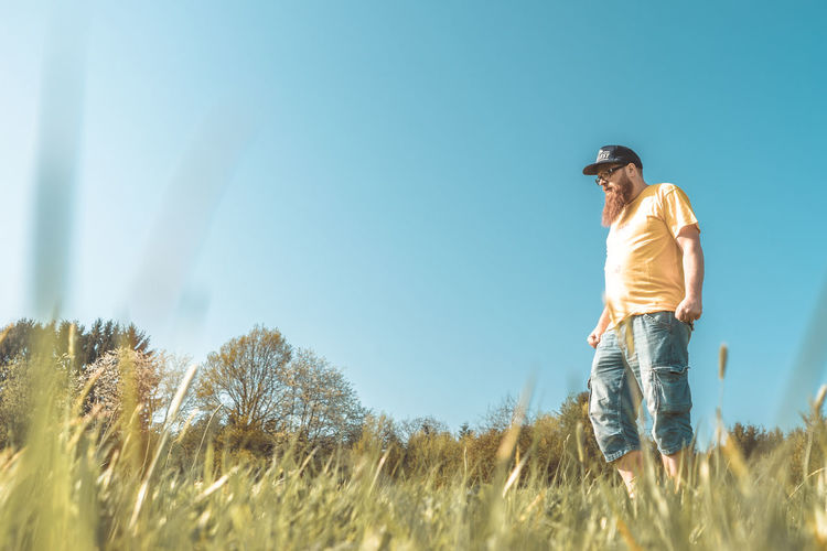 Low Angle View Of Mature Man Standing On Grassy Field Against Clear Blue Sky