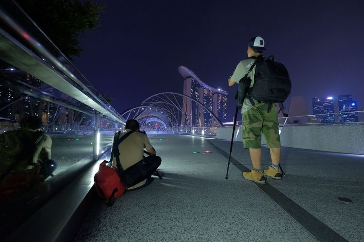 Full Length Rear View Of Photographers Photographing Marina Bay Sands Against Sky At Night