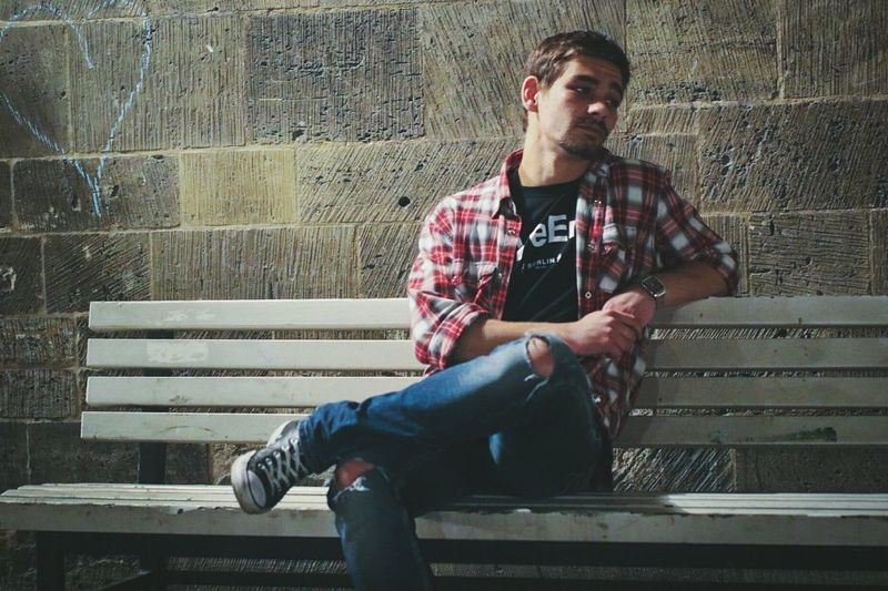 Thoughtful man looking away while sitting on bench