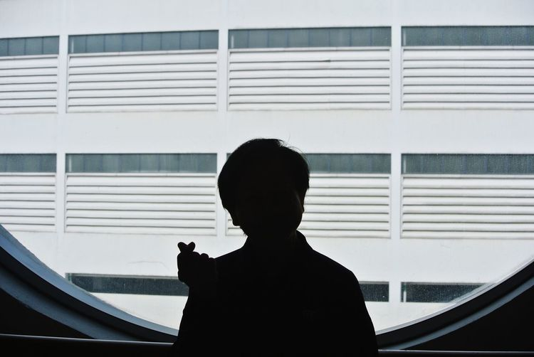 Silhouette man looking through window