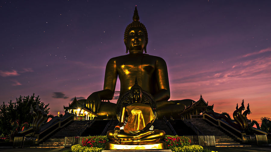 Low angle view of golden buddha statues against star field