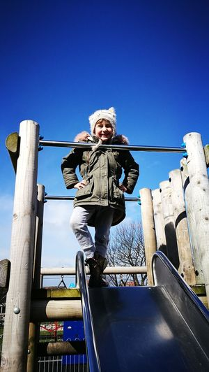 Low angle view of smiling girl standing on slide during sunny day