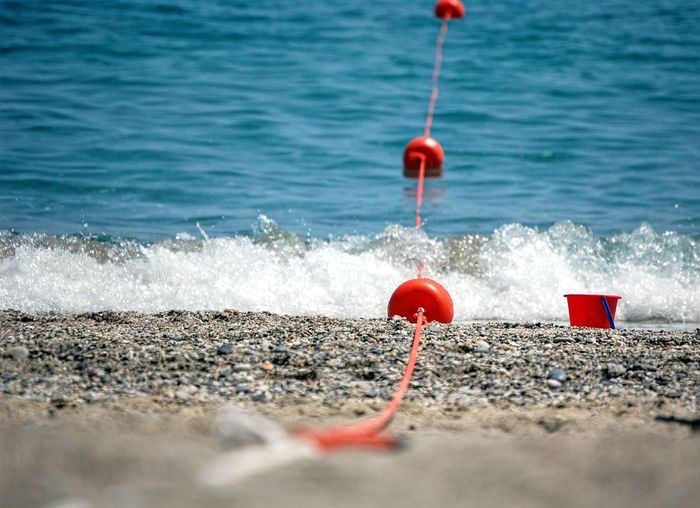 Close-up of red buoys on beach