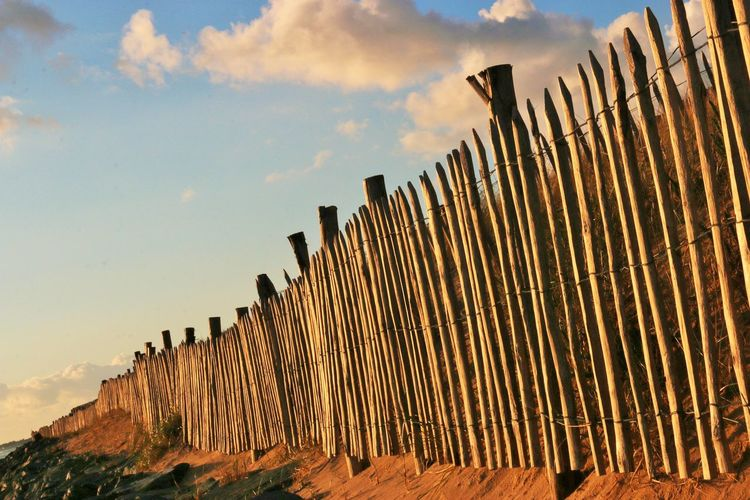 Low angle view of wooden fence against sky on sunny day