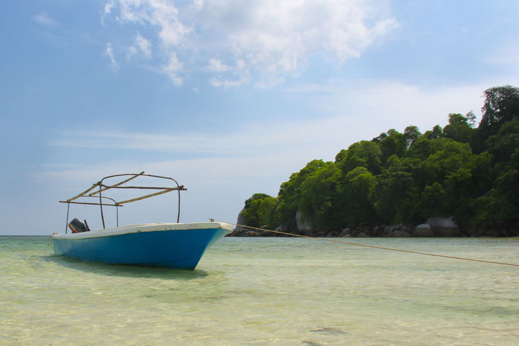 A blue boat on the beautiful clear water of Belitung island Belitung Island Belitung, Indonesia INDONESIA Tropical Paradise Beauty In Nature Cloud - Sky Day Fishing Boat Mode Of Transportation Moored Nature Nautical Vessel No People Outdoors Plant Scenics - Nature Sea Sky Tranquil Scene Tranquility Transportation Tree Turquoise Colored Water Waterfront