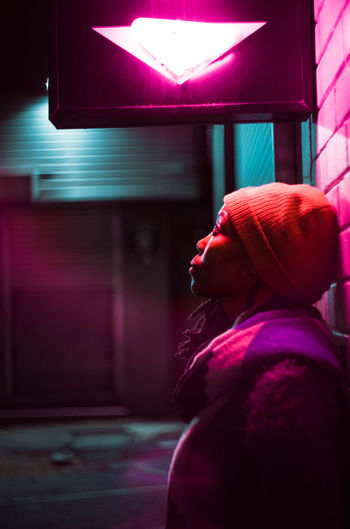 Side view of woman standing by wall at night