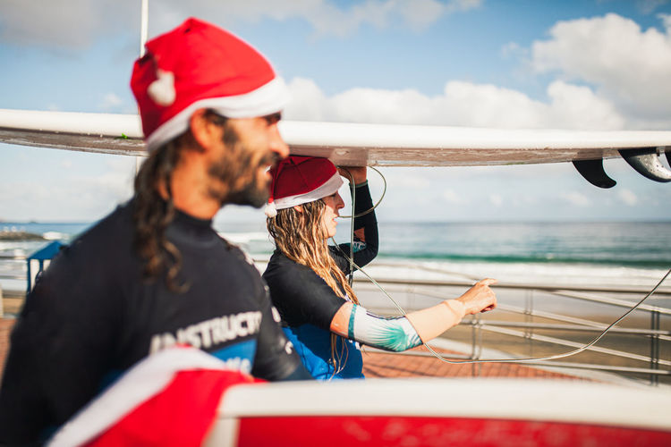 Side view of couple wearing santa hats carrying surfboards on heads