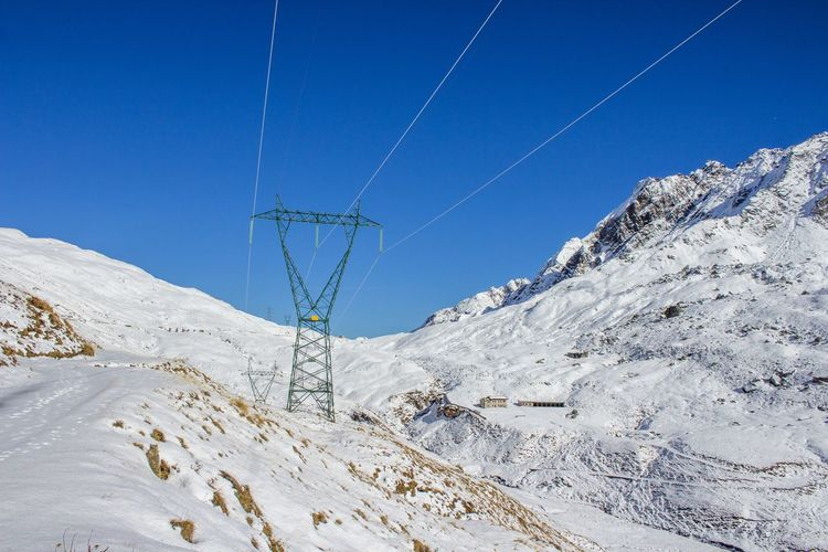 Power line on snow covered mountain against blue sky