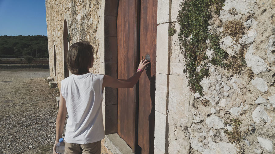 Building Building Exterior Man Boy Crete Crete Greece EyeEmNewHere Sunny Sunny Day Pilgrim Young Man Teenager Teenage Boys Teenagers  One Person One Person Only Door Doorway Doors Door Knocker Rapper Knocker Knocking Knock Men Standing Architecture Closed One Teenage Boy Only 2018 In One Photograph It's About The Journey Moments Of Happiness