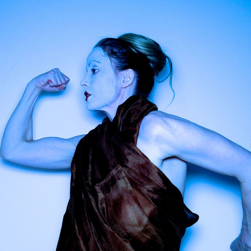 Woman flexing muscle against wall