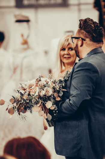 Man talking with woman while holding bouquet