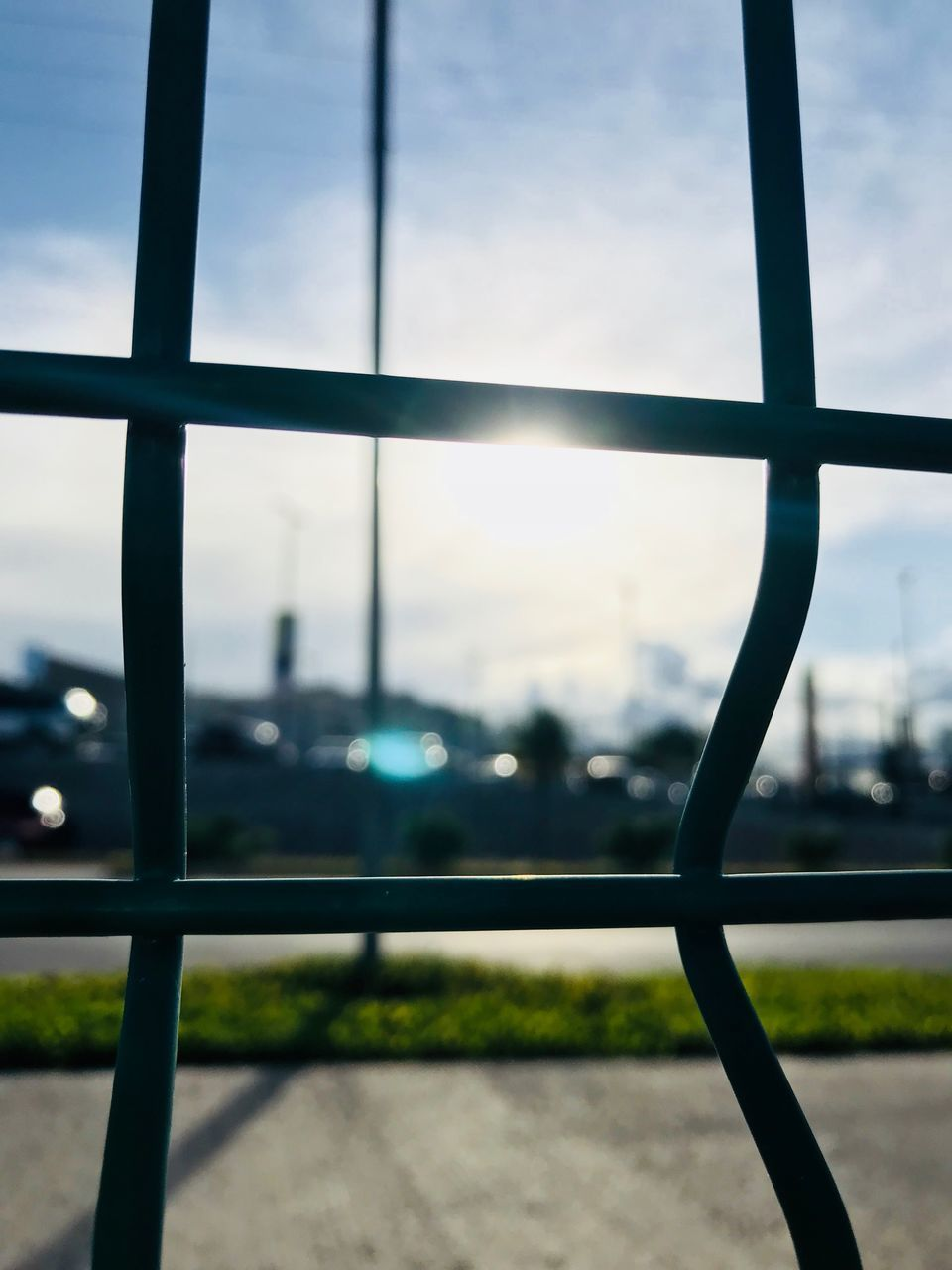 sky, fence, barrier, focus on foreground, no people, boundary, metal, day, nature, safety, close-up, security, transportation, window, outdoors, cloud - sky, protection, airport, grid, railing