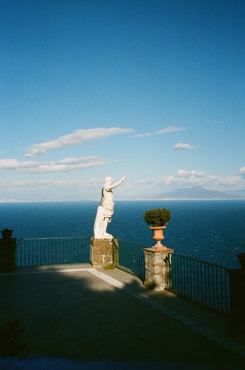 Statue by sea against blue sky