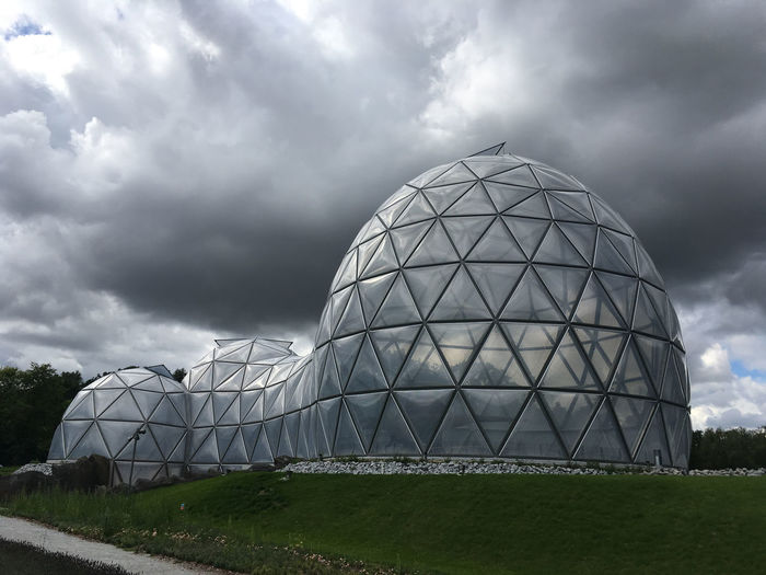 Built structure on field against cloudy sky