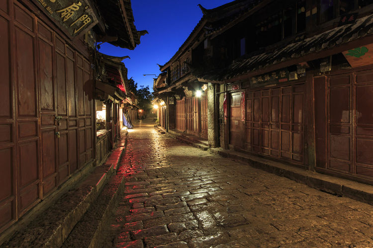 Illuminated Alley Amidst Traditional Houses At Dusk