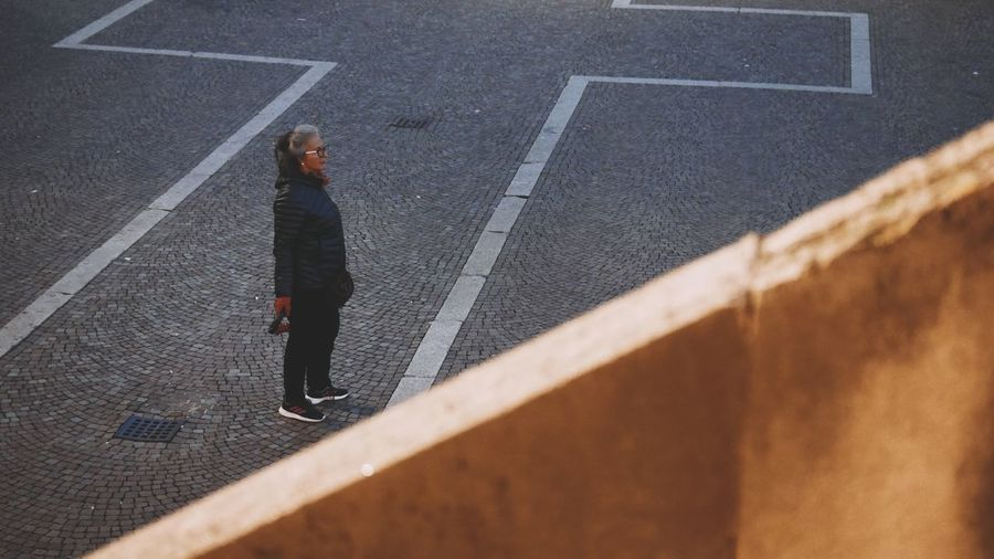High angle view of woman standing on road
