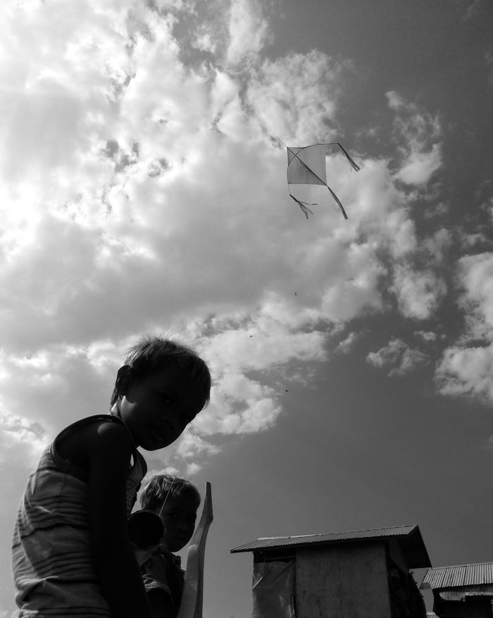 LOW ANGLE VIEW OF BOY STANDING BY SKY