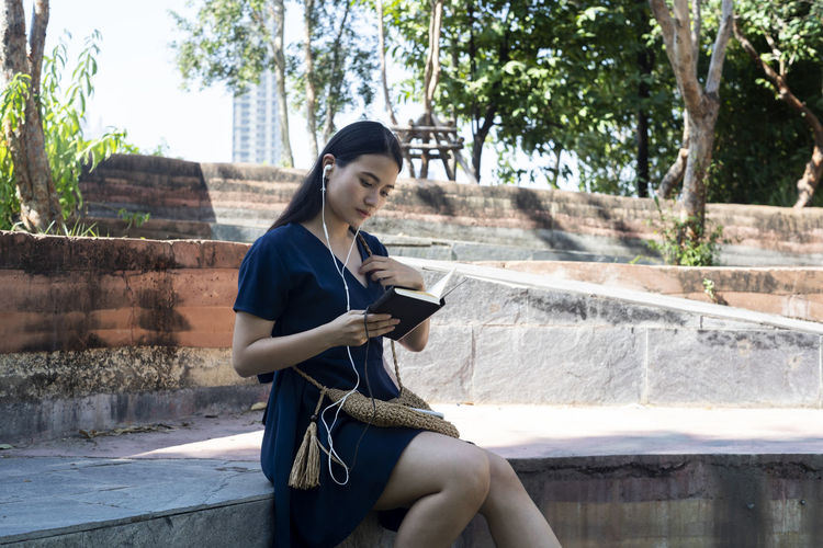 Young woman using mobile phone while sitting on tree