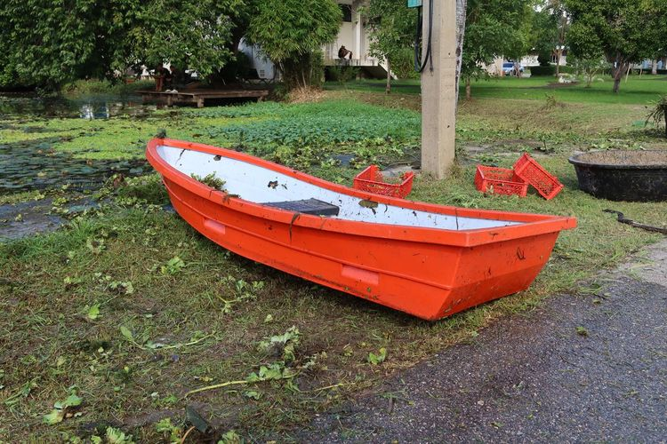 Red boat moored on land