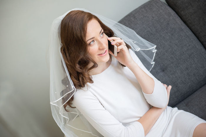 bride on their wedding morning, talking on the cell phone Abdomen Adult Adults Only Bride Casual Clothing Comunication Conversation Day Holding Illness Indoors  Mobile Phone Morning One Person One Woman Only One Young Woman Only People Portrait Sitting Technology Veil Wedding Moment Women Young Adult Young Women